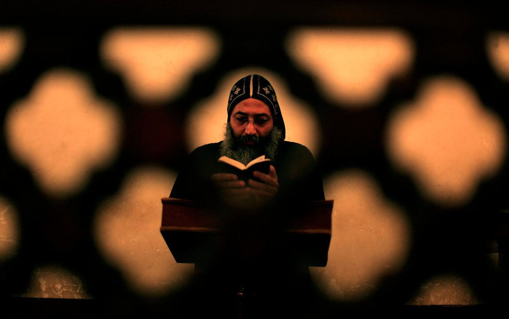 Description of . A clergyman prays during an early morning mass at  the historic al-Muharraq Monastery, a centuries-old site some 180 miles (300 kilometers) south of Cairo in the province of Assiut, Egypt, Tuesday, Feb. 5, 2013. Egypt\'s Coptic Christian pope sharply criticized the country\'s Islamist leadership in an interview with The Associated Press on Tuesday, saying the new constitution is discriminatory and Christians should not be treated as a minority. (AP Photo/Khalil Hamra)