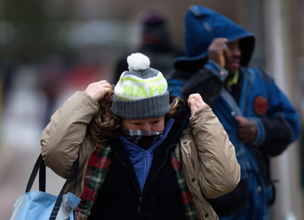 """. Berta Sosa adjusts her coat as she crosses Walker Street on her way to work, Tuesday, Jan. 28, 2014, in Houston. \""""I\'m very cold and it\'s only going to get worse,\"""" she said. (AP Photo/Houston Chronicle, Cody Duty)"""