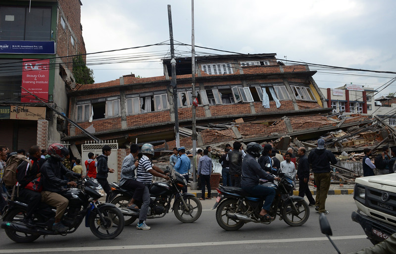 . Nepalese people on motorbikes ride past a collapsed bullding in Kathmandu after an earthquake on April 25, 2015. A massive 7.8 magnitude earthquake killed hundreds of people April 25 as it ripped through large parts of Nepal, toppling office blocks and towers in Kathmandu and triggering a deadly avalanche that hit Everest base camp. PRAKASH MATHEMA/AFP/Getty Images