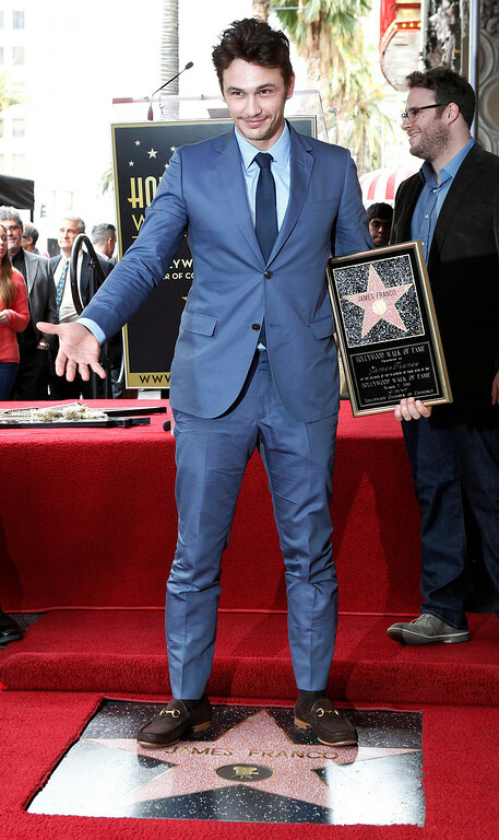 . Actor James Franco stands atop his newly unveiled star on the Hollywood Walk of Fame, as actor Seth Rogen is seen in the background, March 7, 2013. REUTERS/Fred Prouser