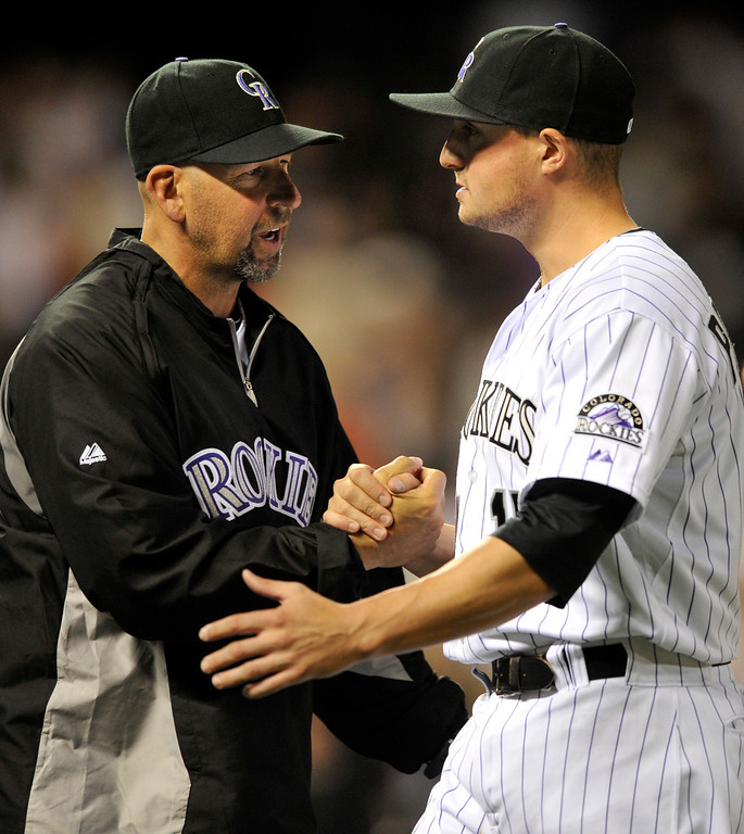 . Colorado Rockies manager Walt Weiss congratulates Jordan Pacheco following a baseball game against the San Francisco Giants on Friday, May 17, 2013, in Denver. Colorado defeated San Francisco 10-9. (AP Photo/Jack Dempsey)