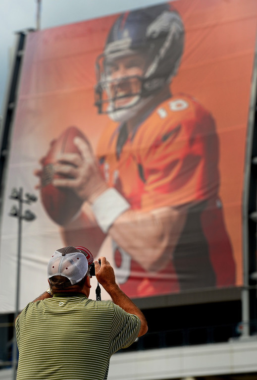 . Tourist Dan Mescher, of Ohio, takes a picture of the large banner of Denver Broncos quarterback Peyton Manning hanging on the outside of Sports Authority Field at Mile High  in Denver on Tuesday September 4, 2013. Denver is hosting  the NFL season opener with the Denver Broncos taking on the Baltimore Ravens Thursday night.  Photo by Helen H. Richardson/The Denver Post