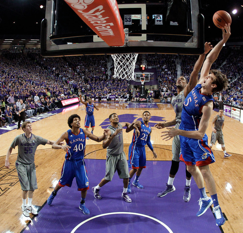 . Kansas center Jeff Withey (5) gets past Kansas State guard Shane Southwell to put up a shot during the first half of an NCAA college basketball game Tuesday, Jan. 22, 2013, in Manhattan, Kan. (AP Photo/Charlie Riedel)