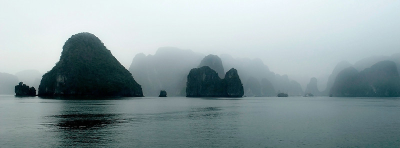 View of Ha Long Bay. The bay consists of a dense cluster of over 3,000 limestone monolithic islands (although locals claim there are only 1,969 as this is the year of Ho Chi Minh's death), each topped with thick jungle vegetation, rising spectacularly from the ocean. 