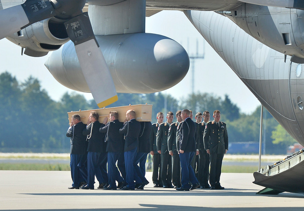 . Soldiers unload coffins during a ceremony to mark the return of the first bodies, of passengers and crew killed in the downing of Malaysia Airlines Flight 17, from Ukraine at Eindhoven military air base, Wednesday, July 23, 2014. After being removed from the planes, the bodies are to be taken in a convoy of hearses to a military barracks in the central city of Hilversum, where forensic experts will begin the painstaking task of identifying the bodies and returning them to their loved ones. (AP Photo/Martin Meissner)