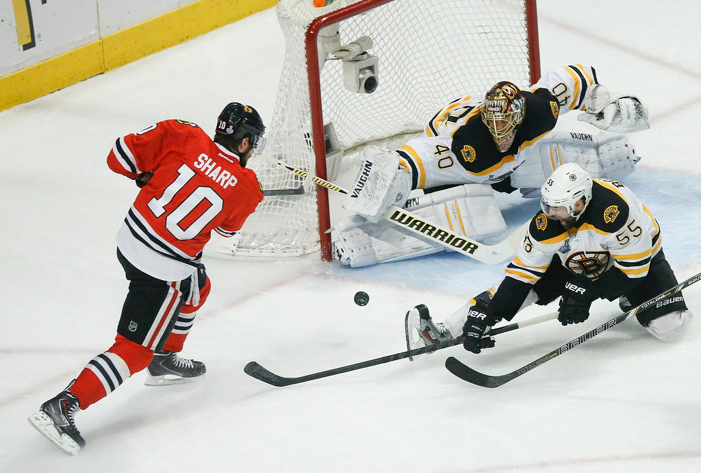 . Chicago Blackhawks center Patrick Sharp (10) shoots the puck against Boston Bruins goalie Tuukka Rask (40) as Boston Bruins defenseman Johnny Boychuk (55) helps defend in the first period during Game 5 of the NHL hockey Stanley Cup Finals, Saturday, June 22, 2013, in Chicago. Chicago Blackhawks defenseman Nick Leddy (8) scored a goal on the rebound. (AP Photo/Charles Rex Arbogast)