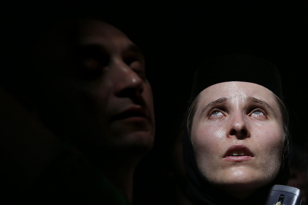 """. Christian Orthodox worshippers look up as a ray of light comes through a skylight in the Church of the Holy Sepulchre in Jerusalem\'s old city on April 19, 2014 during the \""""Holy Fire\"""" ceremony on the eve of the Orthodox Easter. AFP PHOTO/GALI TIBBON/AFP/Getty Images"""