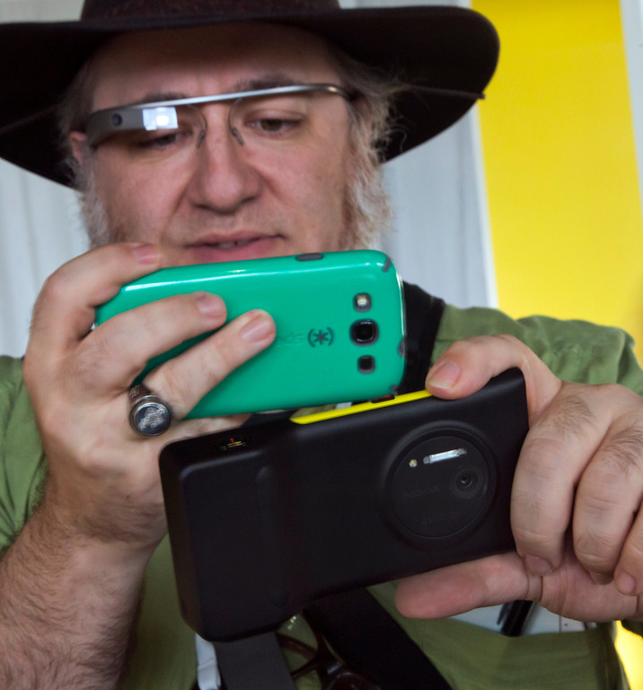 . Journalist Andy Inahtko, from Chicago, wearing Google Glass, uses a smartphone to photograph a Nokia Lumia 1020 at its introduction,  in New York,  Thursday, July 11, 2013.(AP Photo/Richard Drew)