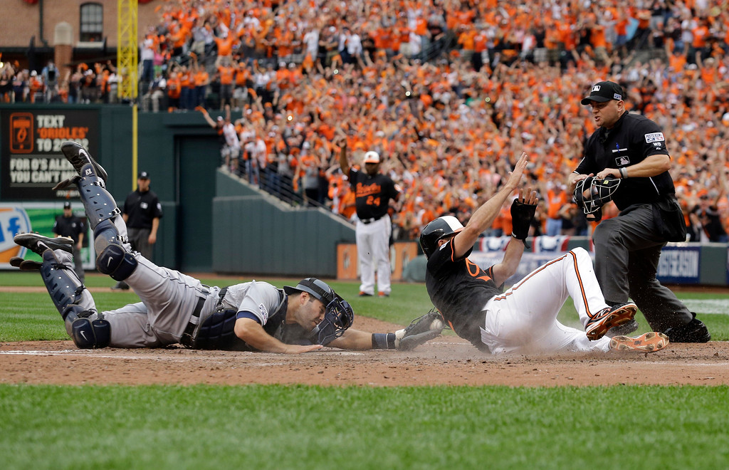 . Detroit Tigers catcher Alex Avila, left, reaches but can\'t make the tag in time as Baltimore Orioles\' J.J. Hardy scores on a double by Delmon Young in the eighth inning of Game 2 in baseball\'s AL Division Series in Baltimore, Friday, Oct. 3, 2014. Baltimore won 7-6. (AP Photo/Patrick Semansky)