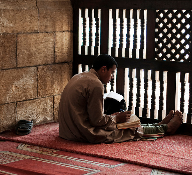 Young man studies the Koran in the calmness of the Al-Azhar mosque.  Cairo, Egypt, 2010.