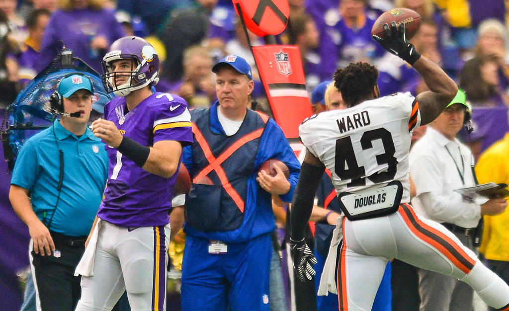 . Browns strong safety T.J. Ward, right, celebrates his second-quarter interception as Vikings quarterback Christian Ponder, left, walks off the field.  (Pioneer Press: Ben Garvin)