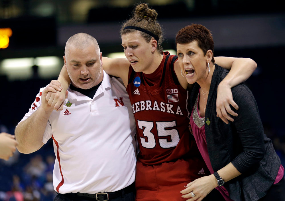 Description of . Nebraska forward Jordan Hooper (35) is helped off the court after being injury during the second half of a regional semifinal game against Duke of the women\'s NCAA college basketball tournament on Sunday, March 31, 2013, in Norfolk, Va.  Duke won 53-45.  (AP Photo/Steve Helber)