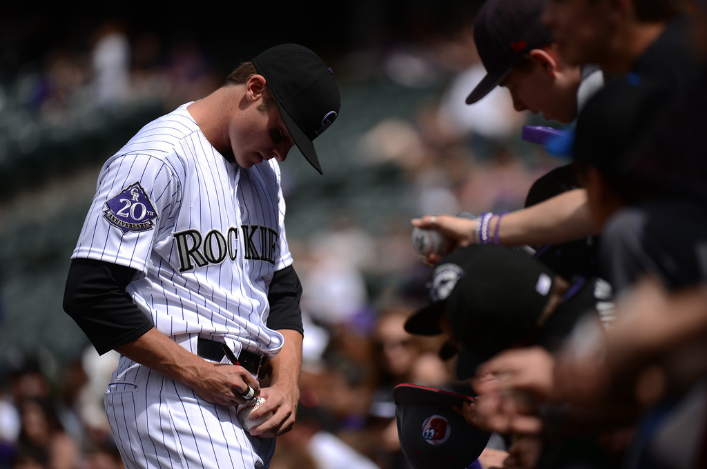 . Josh Rutledge (14) of the Colorado Rockies signs autographs before the start of the first inning. (Photo by Hyoung Chang/The Denver Post)