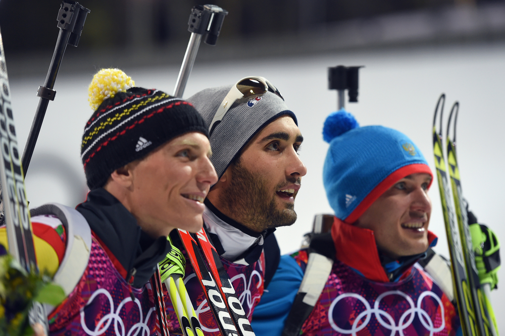 . (L-R) Silver medalist Erik Lesser of Germany, gold medalist Martin Fourcade of France and bronze medalist Evgeniy Garanichev of Russia celebrate on the podium during the flower ceremony for the Men\'s Individual 20 km during day six of the Sochi 2014 Winter Olympics at Laura Cross-country Ski & Biathlon Center on February 13, 2014 in Sochi, Russia.  (Photo by Harry How/Getty Images)