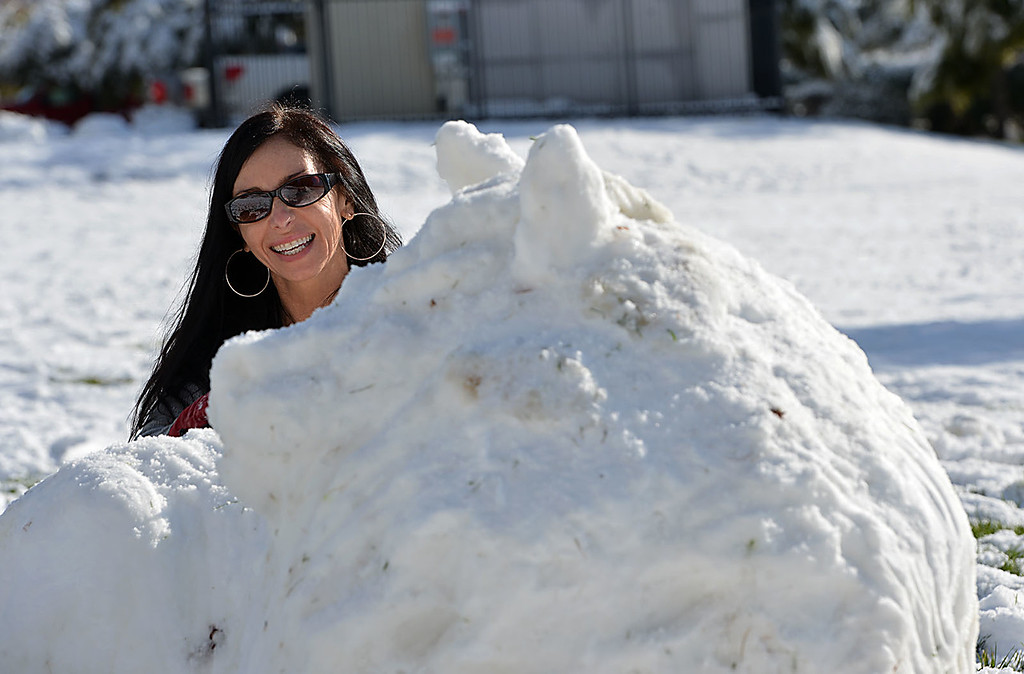 . Jeannette Kantzalis, 51, of Yucapia works on a snow sculpture at Yucaipa Regional Park. Residents of Yucaipa, Calif., awoke Wednesday December 31, 2014 to a blanket of snow left behind by Tuesday\'s winter storm with weather reports claiming three to five inches of snow. (Staff photo by Rick Sforza/The Sun)
