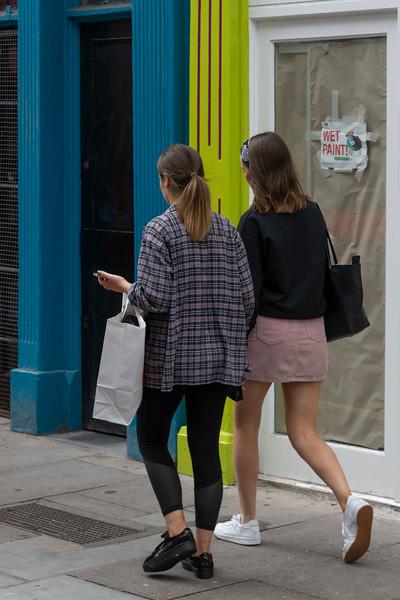 Two women walking on sidewalk, City of Cork, County Cork, Ireland