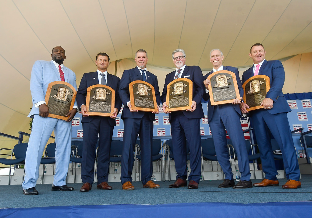 . Baseball Hall of Famers from left, Vladimir Guerrero, Trevor Hoffman, Chipper Jones, Jack Morris, Alan Trammell, and Jim Thome, hold their plaques after an induction ceremony at the Clark Sports Center on Sunday, July 29, 2018, in Cooperstown, N.Y. (AP Photo/Hans Pennink)