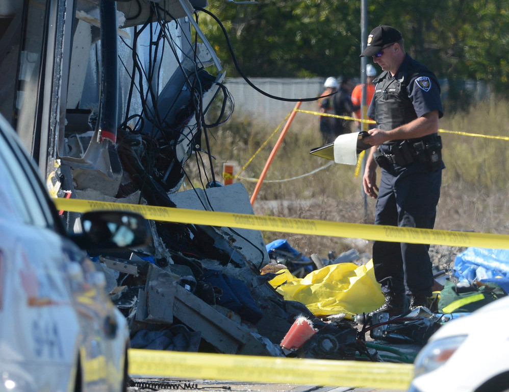 . A police officer checks the scene following a Via Rail train and city bus collision in Ottawa\'s west end Wednesday, Sept. 18, 2013.  The collision at a level crossing took place at the peak of the morning commute. Passengers on the bus say they screamed at the driver to stop just before the crash, and witnesses on the ground said the bus plowed directly into the side of the passing, four-car train. (AP Photo/The Canadian Press, Adrian Wyld)