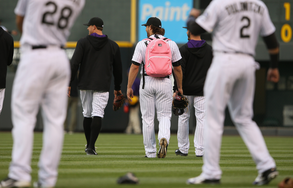 . Rookie pitcher Tommy Kahnle #54 of the Colorado Rockies wears a pink backpack as he and his peers head to the bullpen as the Rockies prepare to face the San Francisco Giants at Coors Field on April 22, 2014 in Denver, Colorado. The Rockies defeated the Giants 2-1.  (Photo by Doug Pensinger/Getty Images)