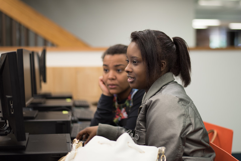 Miesha Jones(right) helping Tishauna Robison setting up her Spring Semester schedule at the library.
