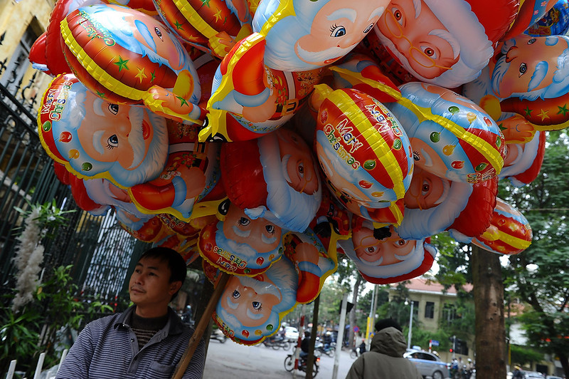 . A vendor stands selling Santa Claus balloons outside a church in downtown Hanoi on December 24, 2012. Churches, shops, restaurants and shopping malls are decorated in the Southeast Asian communist nation where some 6 million catholics are preparing to celebrate Christmas. HOANG DINH NAM/AFP/Getty Images