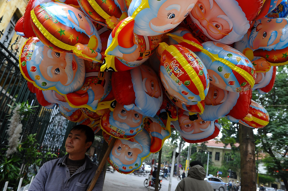 Description of . A vendor stands selling Santa Claus balloons outside a church in downtown Hanoi on December 24, 2012. Churches, shops, restaurants and shopping malls are decorated in the Southeast Asian communist nation where some 6 million catholics are preparing to celebrate Christmas. HOANG DINH NAM/AFP/Getty Images