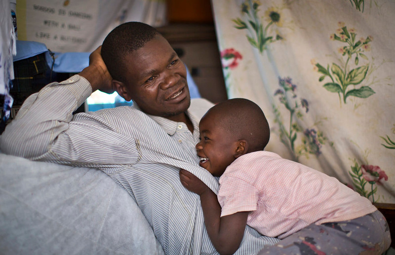 . Former Westgate Mall security guard David Odhiambo, 36, recounts his experience as his daughter Benta, 4, plays with him in his tiny, one-room house where he lives with his wife and five children in the Kawangware slum of Nairobi, Kenya on Aug. 27, 2014. Odhiambo was one of the blue-uniformed security guards tasked with protecting Nairobiís Westgate Mall one year ago when four heavily armed terrorists attacked, earning him two bullets in the head. (AP Photo/Ben Curtis)