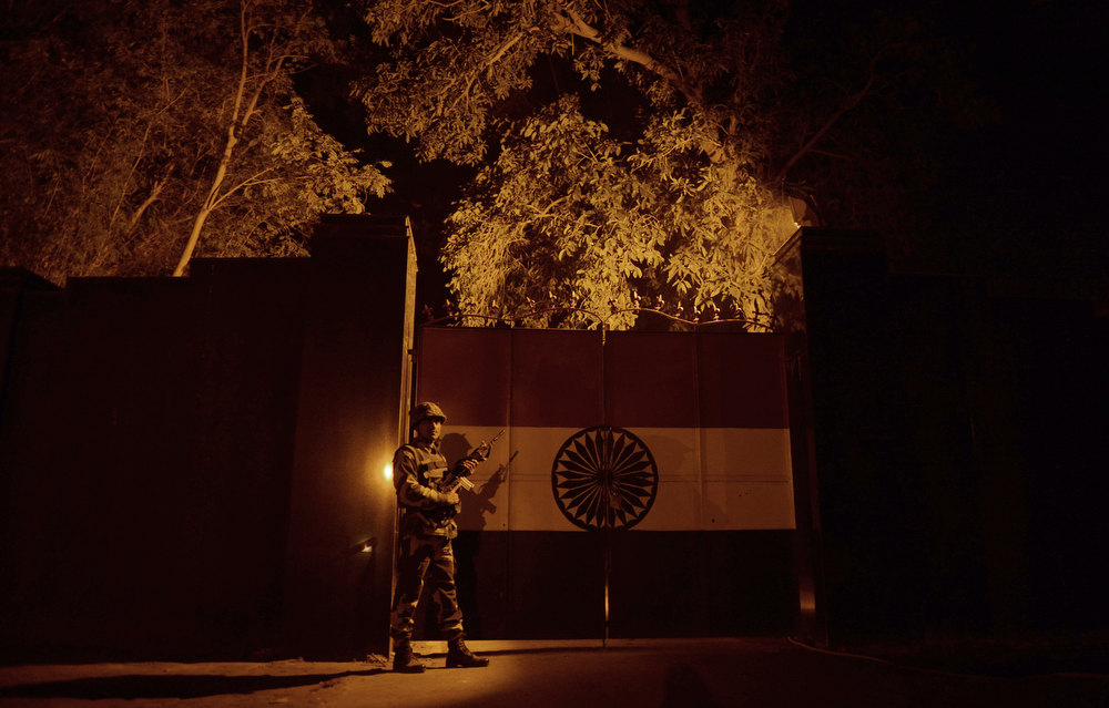 ". An Indian Border Security Force (BSF) soldier stands guard near a gate at an outpost along the India-Pakistan border in Suchit-Garh, 36 kms southwest of Jammu on January 11, 2013. Pakistan summoned the Indian ambassador to protest against ""unacceptable and unprovoked\"" attacks by the Indian army that killed two Pakistani soldiers in five days in Kashmir. TAUSEEF MUSTAFA/AFP/Getty Images"