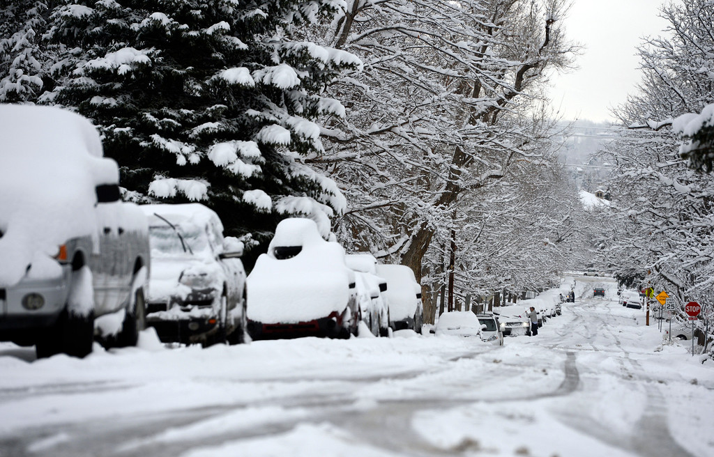 . Pete Hansen cleans snow from his car in Boulder, April 16, 2013, after a spring snow storm hit the area. (Photo By RJ Sangosti/The Denver Post)