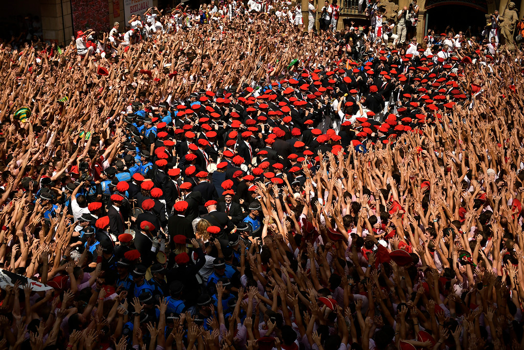 . A municipal brass band makes it\'s away through a crowd of revellers during the launch of the \'Chupinazo\' rocket, to celebrate the official opening of the 2018 San Fermin fiestas with daily bull runs, bullfights, music and dancing in Pamplona, Spain, Friday July 6, 2018. (AP Photo/Alvaro Barrientos)