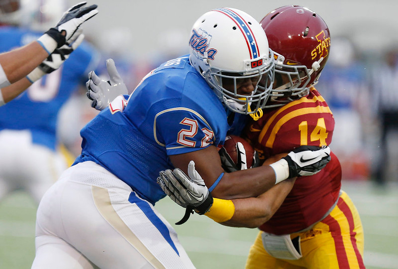 . Tulsa running back Trey Watts (22) is tackled by Iowa State defensive back Jared Brackens (14) after a short gain in the first quarter of the Liberty Bowl NCAA college football game in Memphis, Tenn., Monday, Dec. 31, 2012. (AP Photo/Rogelio V. Solis)
