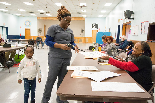 11/05/19 Wesley Bunnell | StaffrrRoberta Clements, 3rd L, hands Trena Edney her voting ballot at the VFW 511 voting location early Tuesday afternoon. Edney is accompanied by her 4 year old daughter Sa'har Register.