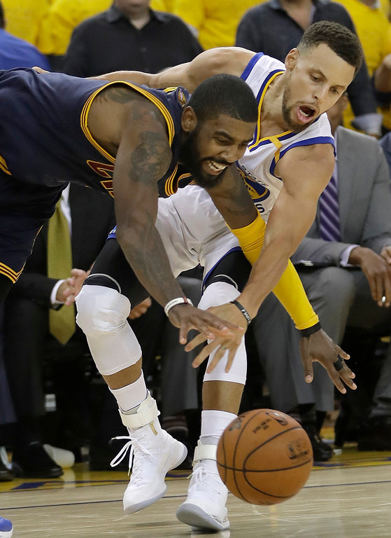 . Golden State Warriors guard Stephen Curry, right, reaches for the ball as he guards Cleveland Cavaliers guard Kyrie Irving during the second half of Game 1 of basketball\'s NBA Finals in Oakland, Calif., Thursday, June 1, 2017. (AP Photo/Marcio Jose Sanchez)