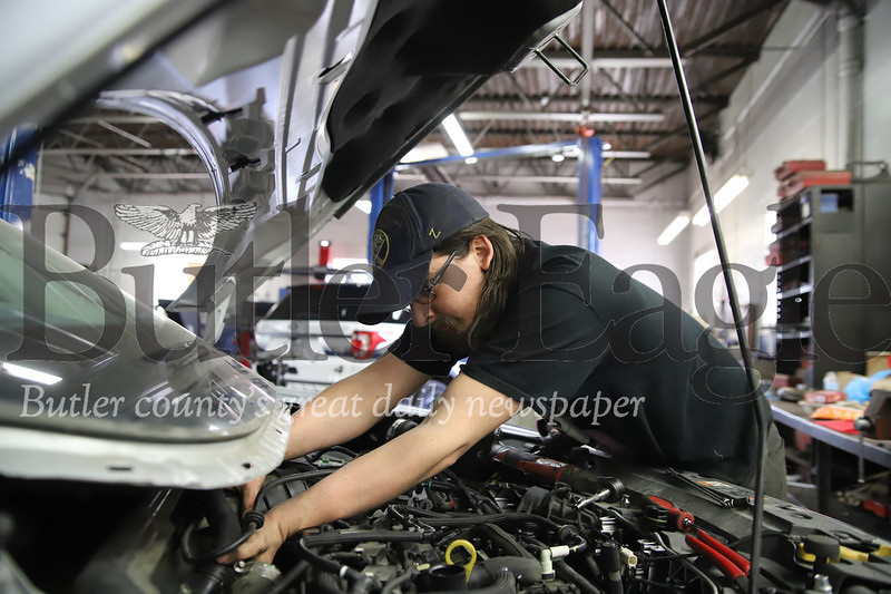 Butler Ford mechanic works on the the engine of a Ford Escape Thursday 4/9/20 in the dealership's automotive repair shop. While car salesman have been unable to sell during the pandemic, mechanics and autobody workers are considered essential personell. Seb Foltz/Butler Eagle