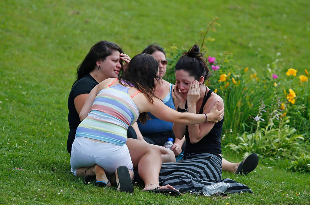 . A woman comforts her friend while they sit on the grass at the Polyvalente Montignac, the school sheltering the people who were forced to leave their houses after the explosion, in Lac Megantic, July 7, 2013. Several people were missing after four tank cars of petroleum products exploded in the middle of a small town in the Canadian province of Quebec early on Saturday in a fiery blast that destroyed dozens of buildings.  REUTERS/Mathieu Belanger