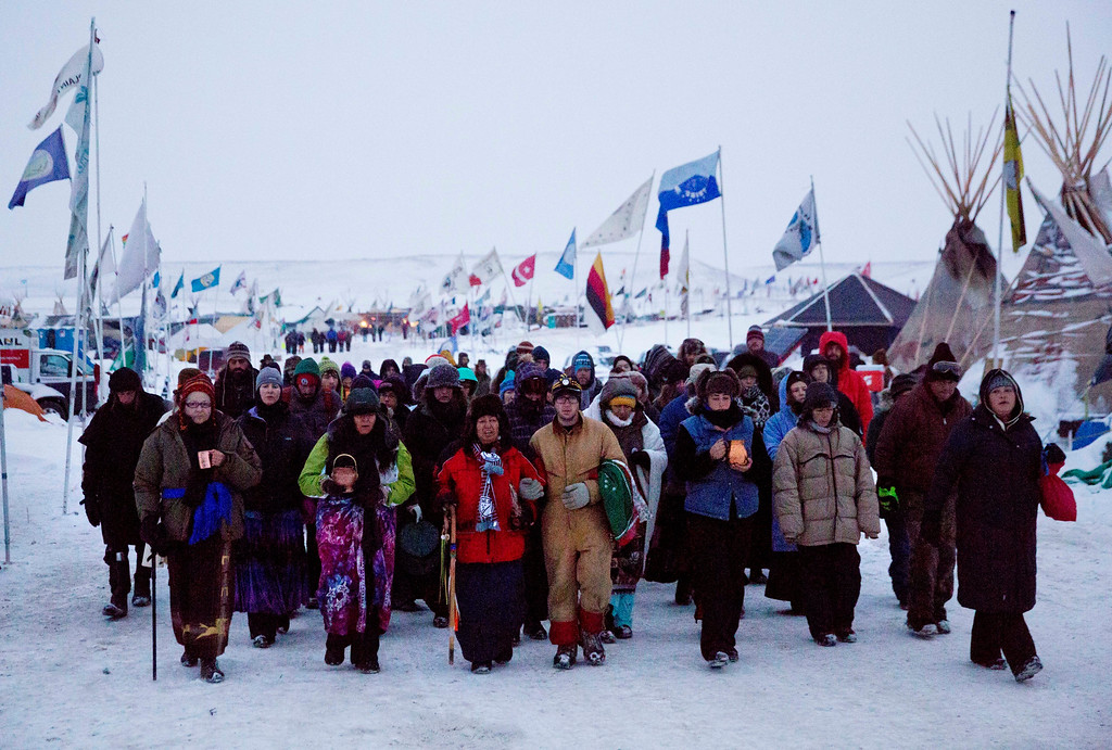 . In this Thursday, Dec. 1, 2016 photo, Beatrice Menase Kwe Jackson, center, walks with Daniel Emory, both of the Ojibwe Native American tribe as they lead a procession to the Cannonball river for a traditional water ceremony at the Oceti Sakowin camp where people have gathered to protest the Dakota Access oil pipeline in Cannon Ball, N.D. The pipeline is largely complete except for a short segment that is planned to pass beneath a Missouri River reservoir. The company doing the building says it is unwilling to reroute the project. (AP Photo/David Goldman)