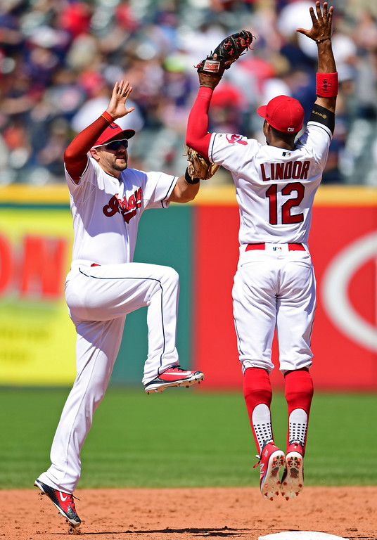 . Cleveland Indians\' Francisco Lindor, right, and Lonnie Chisenhall celebrate after defeating the Detroit Tigers 12-2 in a baseball game, Sunday, June 24, 2018, in Cleveland. (AP Photo/David Dermer)
