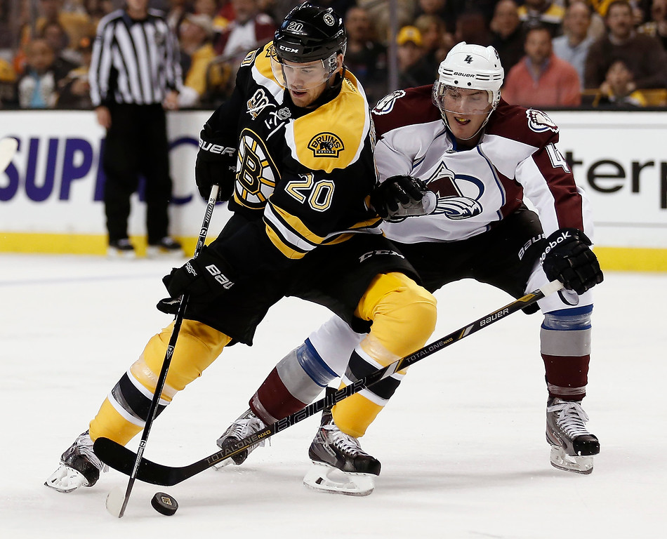 . Boston Bruins\' Daniel Paille (20) tries to get around Colorado Avalanche defenseman Tyson Barrie during the second period of an NHL hockey game in Boston on Thursday, Oct. 10, 2013. (AP Photo/Winslow Townson)