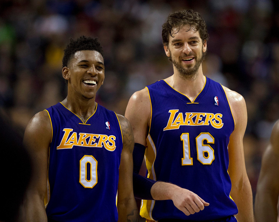 . Los Angeles Lakers center Pau Gasol (16) and guard Nick Young (0) smile as they walk off the court after defeating the Toronto Raptors 112-106 in NBA basketball action in Toronto, Sunday, Jan. 19, 2014. (AP Photo/The Canadian Press, Frank Gunn)