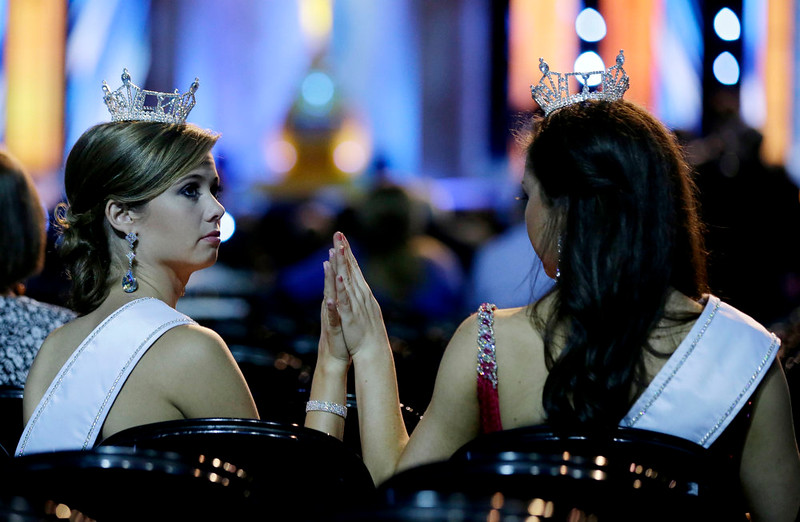 . Miss Florida Outstanding Teen Michaela McLean, 16, left, and Miss Nevada Outstanding Teen Amy Smith, 15, tap hands before the start of the Miss America 2015 pageant, Sunday, Sept. 14, 2014, in Atlantic City, N.J. (AP Photo/Mel Evans)