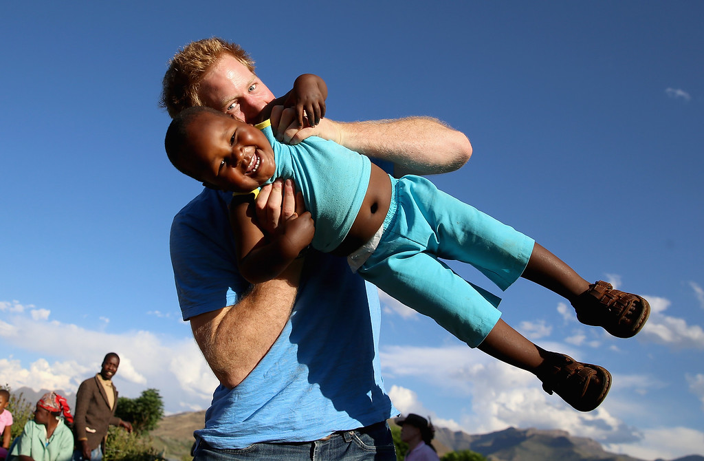 . Prince Harry swings young three year old orphan boy called Lerato in this photograph taken with the help of a three year old blind girl called Karabo during a visit to Phelisanong Children\'s Home on December 6, 2014 in Maseru, Lesotho. (Photo by Chris Jackson - WPA Pool /Getty Images)