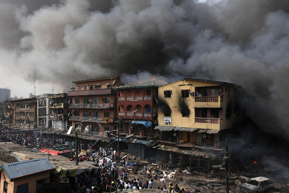 Description of . Residents look  as a fire burns out a residential homes and a warehouse on Lagos Island in Lagos, Nigeria, Wednesday, Dec. 26, 2012. An explosion ripped through a warehouse Wednesday where witnesses say fireworks were stored in Nigeria's largest city, sparking a fire. It wasn't immediately clear if anyone was injured in the blast that firefighters and locals struggled to contain. (Ap Photos/Sunday Alamba)