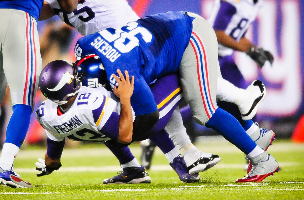 . Vikings quarterback Josh Freeman gets taken down hard by Giants defensive tackle Shaun Rogers after a missed throw late in the fourth quarter.  (Pioneer Press: Ben Garvin)
