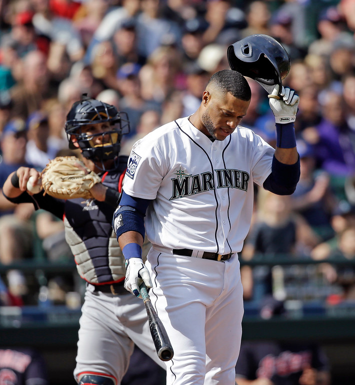 . Seattle Mariners\' Robinson Cano, right, pulls off his batting helmet after striking out to end the third inning as Cleveland Indians catcher Yan Gomes tosses the ball back to the mound in a baseball game Saturday, Sept. 23, 2017, in Seattle. (AP Photo/Elaine Thompson)