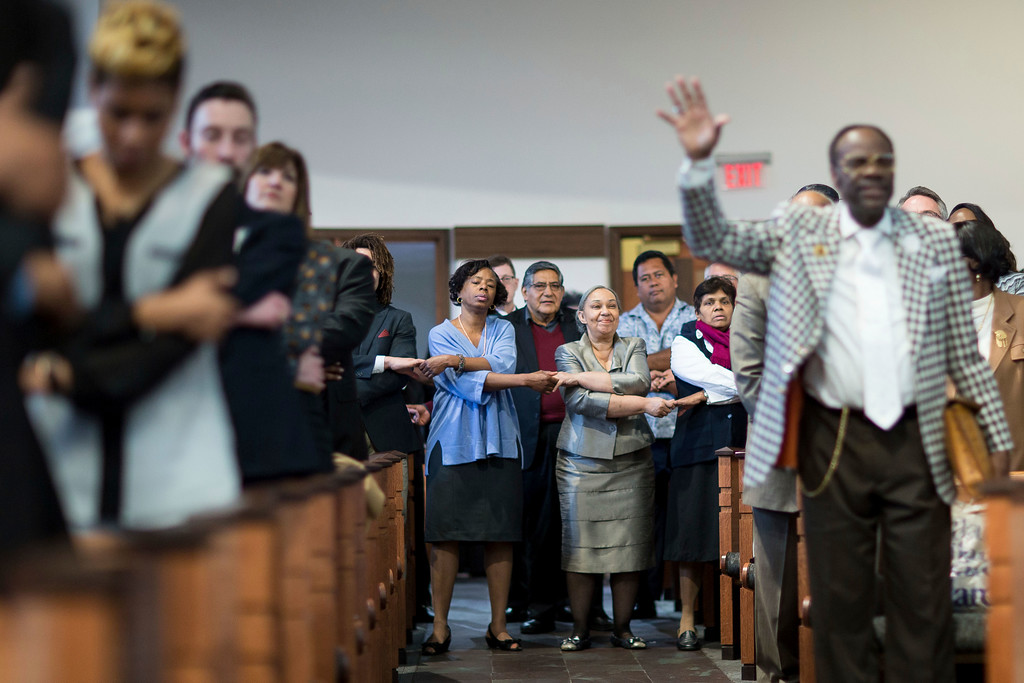 ". Audience members join hands while singing ""We Shall Overcome\"" during a Martin Luther King Jr. holiday commemorative service at Ebenezer Baptist Church, Monday, Jan. 16, 2017, in Atlanta. (AP Photo/Branden Camp)"
