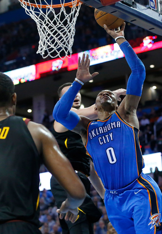 . Oklahoma City Thunder guard Russell Westbrook (0) shoots in front of Cleveland Cavaliers forward Larry Nance Jr., rear, during the second half of an NBA basketball game in Oklahoma City, Tuesday, Feb. 13, 2018. (AP Photo/Sue Ogrocki)