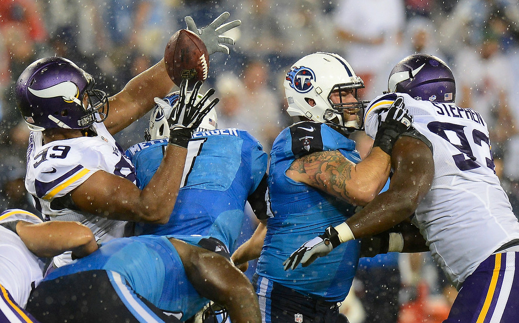 . Minnesota Vikings defensive tackle Corey Wootton (99) grabs the ball after stripping it away from Tennessee Titans quarterback Zach Mettenberger (7) in the second quarter. Tennessee Titans guard Eric Olsen, second from right, blocks Minnesota Vikings defensive tackle Shamar Stephen (93). The Vikings took control of the ball on the play. (AP Photo/Mark Zaleski)