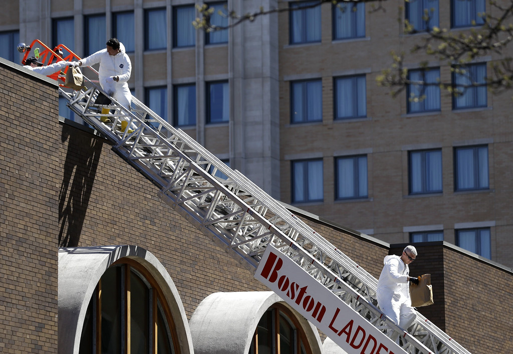. FBI investigators walk down a fire truck ladder with  bags from a building at the corner of Boylston Street and Fairfield Street , Wednesday, April 17, 2013, in Boston. Investigators in white jumpsuits fanned out across the streets, rooftops and awnings around the blast site in search of clues on Wednesday.   (AP Photo/Julio Cortez)