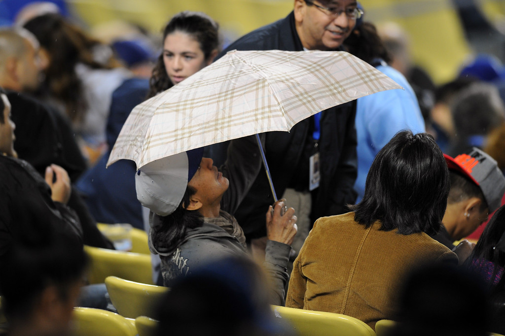 . A fan takes shelter under an umbrella as rain falls on the Dodgers-Rockies game, Friday, April 25, 2014, at Dodger Stadium. (Photo by Michael Owen Baker/L.A. Daily News)