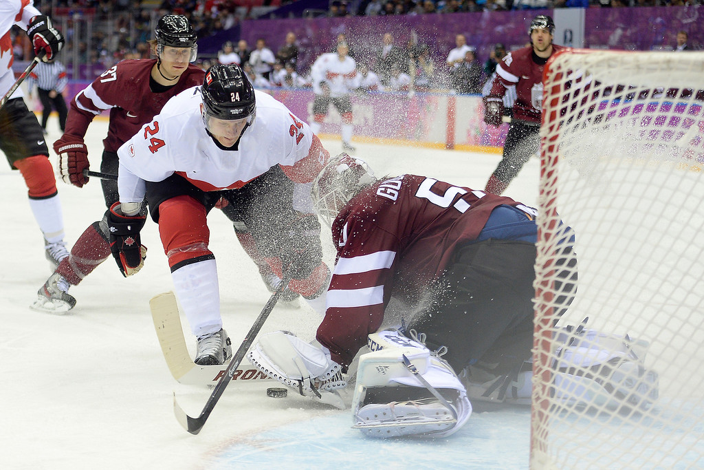 . SOCHI, RUSSIA - FEBRUARY 19: Kristers Gudlevskis (50) of the Latvia makes a stop on Corey Perry (24) of the Canada during the first period of men\'s hockey action. Sochi 2014 Winter Olympics on Wednesday, February 19, 2014 at Bolshoy Ice Arena. (Photo by AAron Ontiveroz/ The Denver Post)